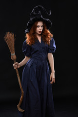 Young beautiful red-haired witch in the dark