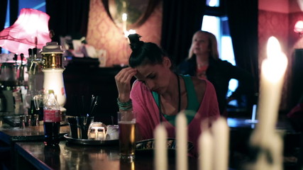Sad woman drinking beer in a pub, steadycam shot