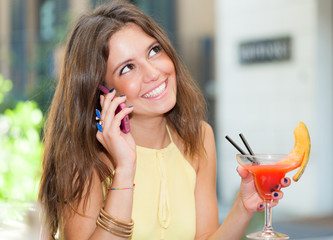 Woman drinking a cocktail and talking on the phone