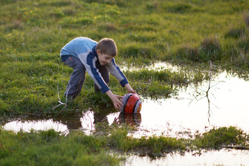 boy gets ball with puddles in the grass
