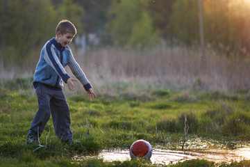 boy dropped the ball in a puddle and shouts
