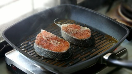 Cooking salmon steaks on the grill pan and lay out on a plate