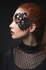 beautiful red-haired girl lace makeup in the dark