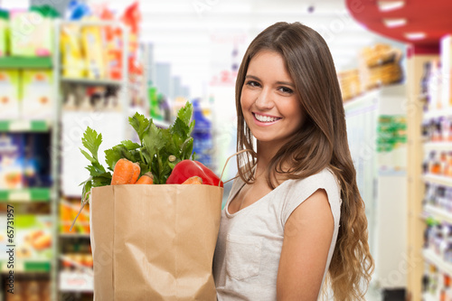 Woman holding a paper shopping bag - 65731957