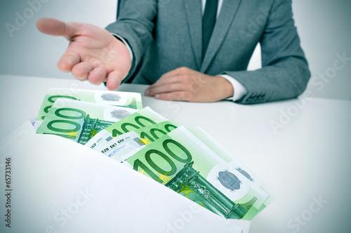man taking an envelope full of euro bills