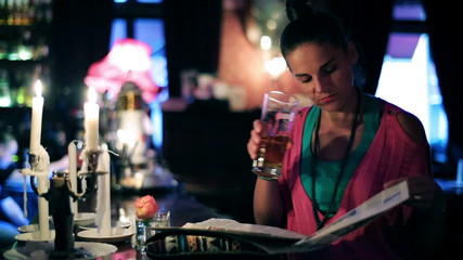 Woman with newspaper drinking beer in a pub, steadycam shot