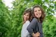 Zwei Mädchen zeigen Zunge im Freien