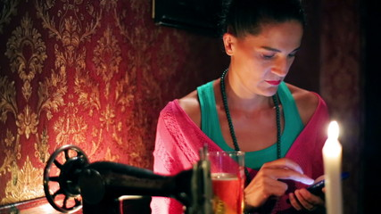 Woman with cellphone sitting in a pub, steadycam shot