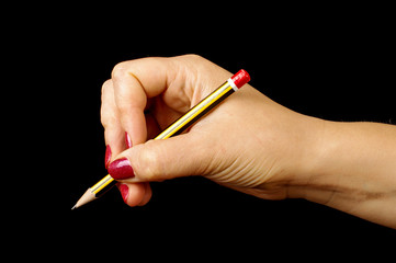Woman hand holding pencil on the black background