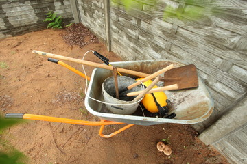 wheelbarrow with building and garden supplies in the yard