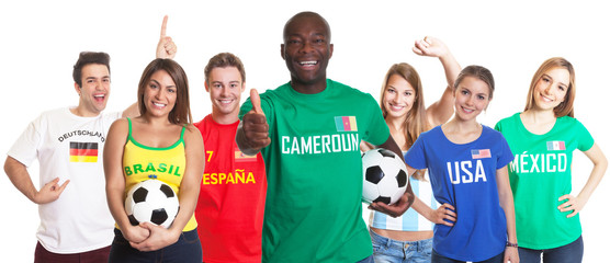 Football fan from Cameroon showing thumb with other fans