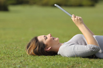 Profile of a happy woman reading a tablet reader on the grass