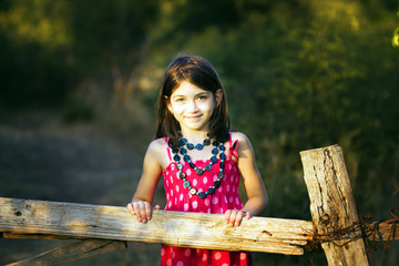 Little girl  front of an old wooden fence