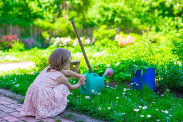 Adorable cute girl with a watering can at big green garden