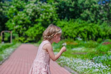 Happy little girl blowing a dandelion in flowering park