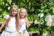 Little adorable girls enjoy weekend in beautiful blooming garden