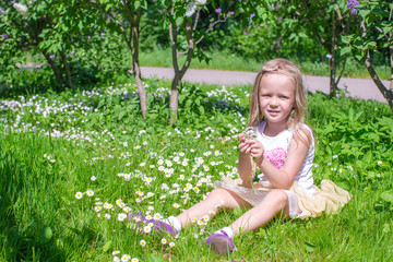Little happy girl picking flowers in green glade