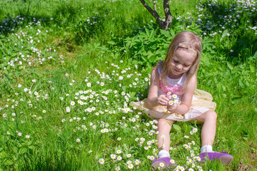 Little adorable girl on flower green glade