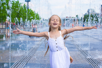 Portrait of little happy girl have fun in street fountain at hot