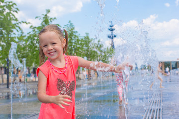 Little adorable girl have fun in street fountain at hot sunny
