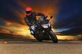young man riding big bike motorcycle on asphalt roads against be