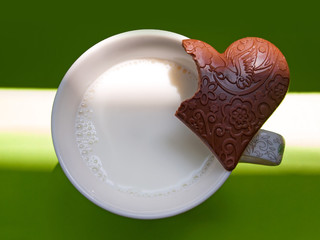 Cup of milk and incomplete heart-shaped chocolate