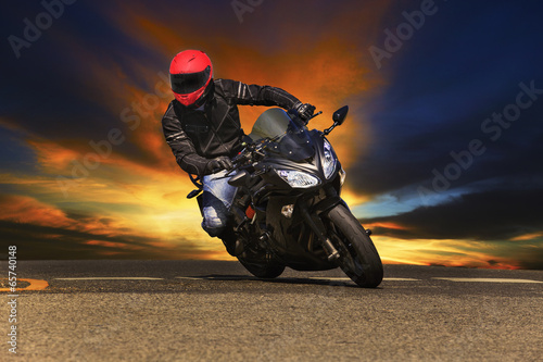 young man riding big bike motorcycle on asphalt roads against be - 65740148