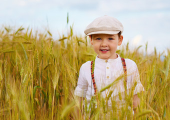 cute smiling boy walking the wheat field