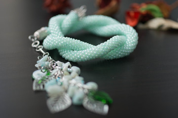 Necklace of mint color on a wooden background