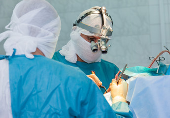 Surgeon with magnifier during the operation.