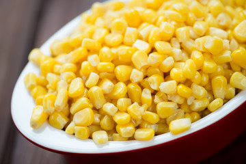 Glass bowl with sweet corn kernels, close-up, horizontal shot