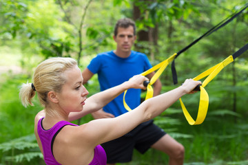 Training with fitness straps outdoors.
