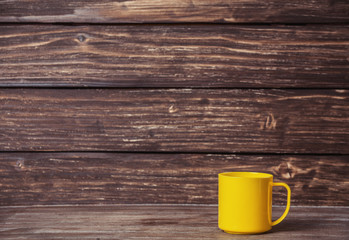 Cup on wooden table and with wood on background