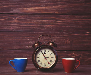 Two tea cup and alalrm clock on wooden table.