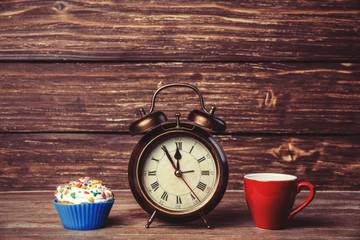 Cup of coffee and cupcake with alarm clock on wooden table.