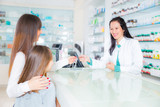 pharmacist  giving vitamins to child girl in pharmacy drugstore