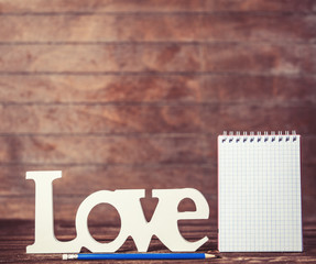 Pencil and notebook with word Love on wooden background.