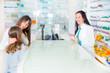 pharmacist  giving vitamins to child girl in pharmacy drugstore