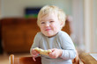 Cute toddler girl eating sandwich in the morning - 65746536