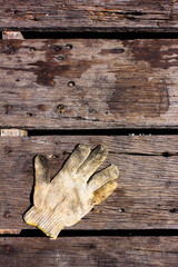 dirty cotton work glove on the wooden floor