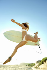 Young attractive surfer jumping onto the beach with surfboard