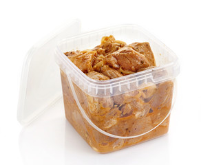 Marinated pork meat pieces in a plastic box