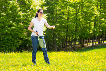 Woman playing badminton on a grassy rural field