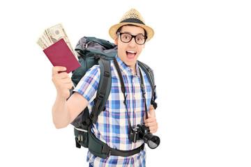 Male tourist holding his passport full of money
