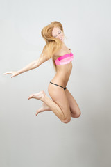 Happy beautiful woman jumping in swimsuit
