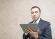 Pensive and serious businessman looking message in tablet comput