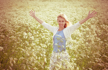 happy young woman in the field of white wild flowers