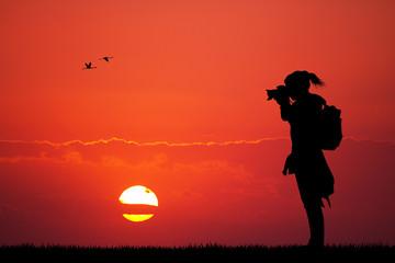 girl photographer at sunset