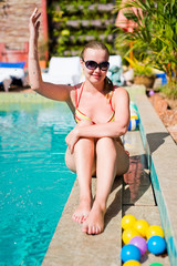 Young Happy woman sitting close to swimming pool