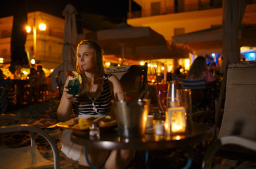 Woman enjoying a drink in pub or restaurant
